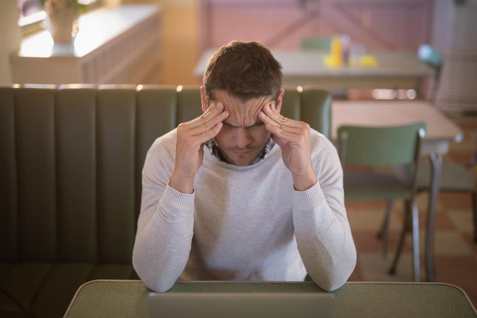 """Depressed man sitting in restaurant"" stock image"