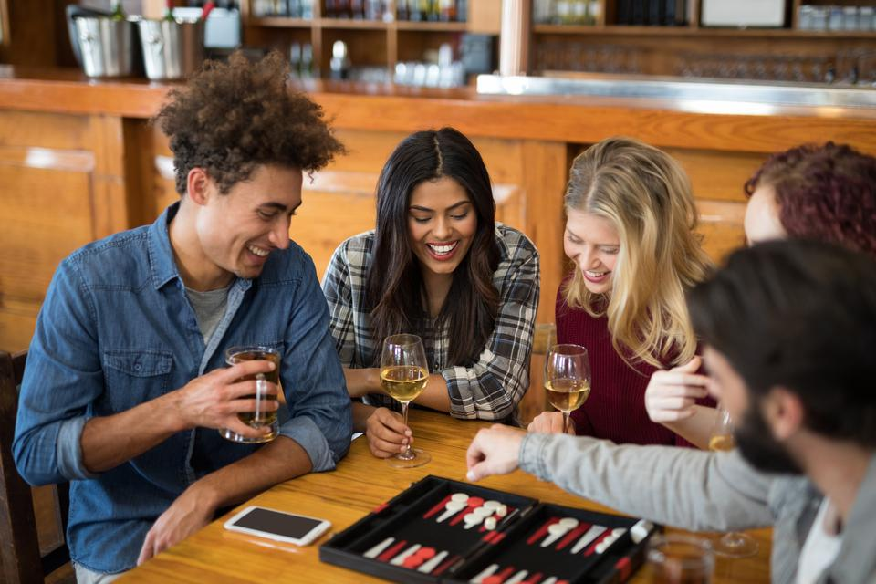 """""""Friends playing backgammon while having drinks in bar"""" stock image"""