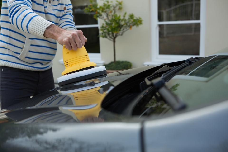 """Auto service staff cleaning a car bonnet with rotating wash brush"" stock image"
