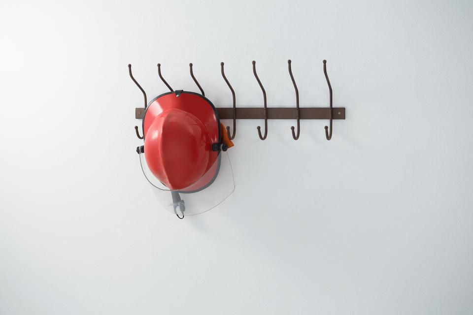 """Red hardhat hanging on hook"" stock image"