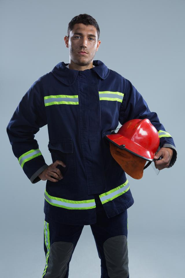 """Fireman standing with hand on hip"" stock image"