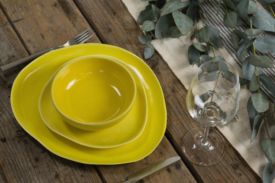 """""""Stack of various dinnerware with cutlery and empty glass"""" stock image"""