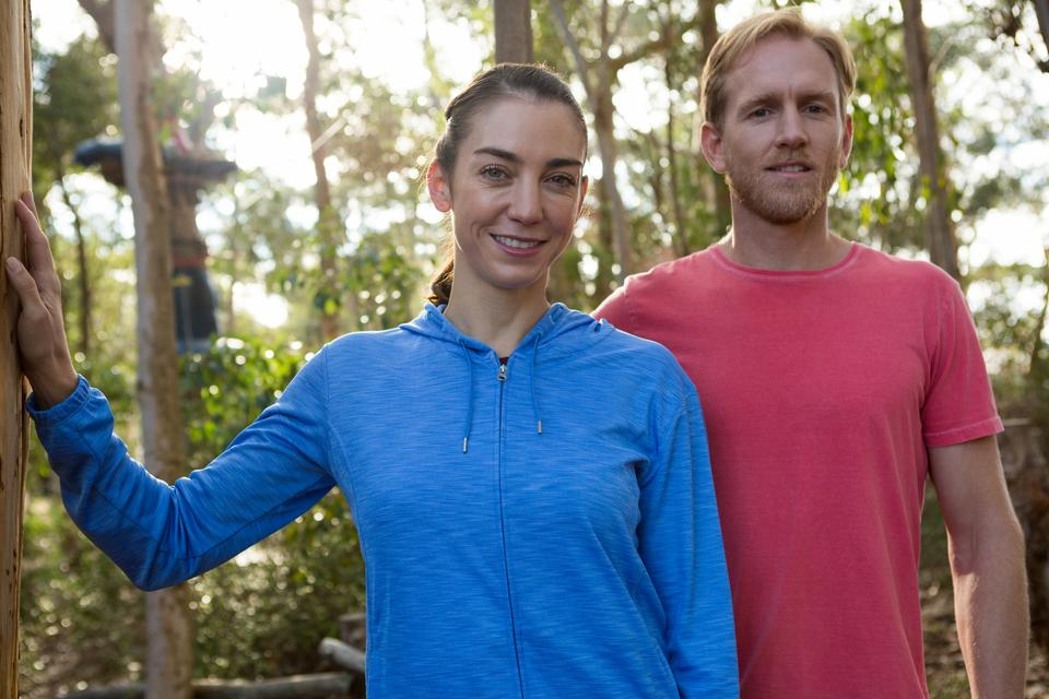 """""""Man and woman trainer standing together in forest"""" stock image"""