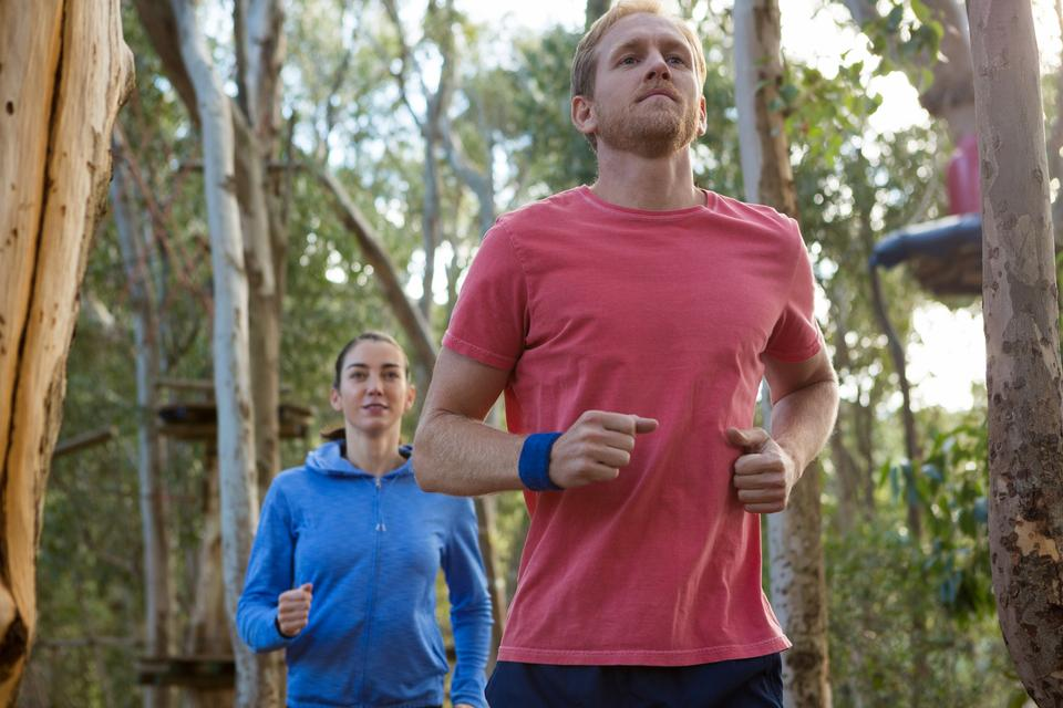 """Man and woman jogging in forest"" stock image"