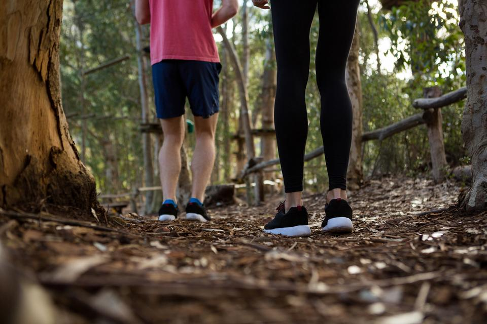 """Legs of man and woman standing in forest"" stock image"