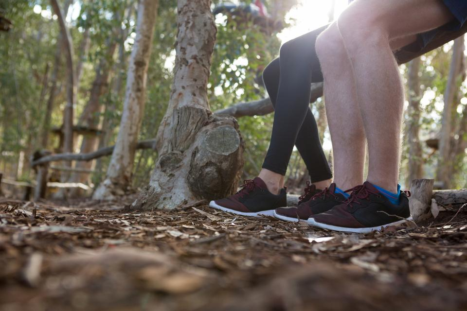 """Legs of man and woman sitting on log of wood in the forest"" stock image"