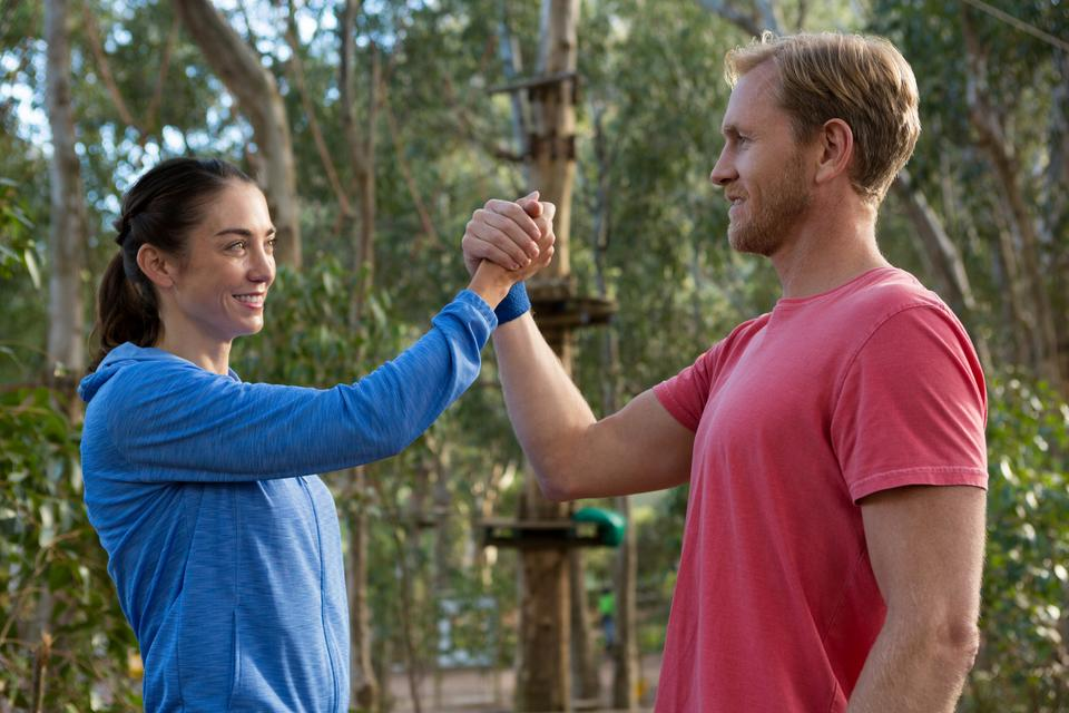 """""""man and woman giving hi-five on a sunny"""" stock image"""