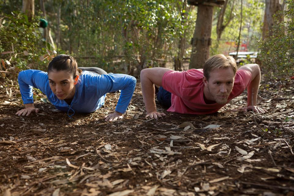 """""""Woman and man doing push ups on a sunny day"""" stock image"""