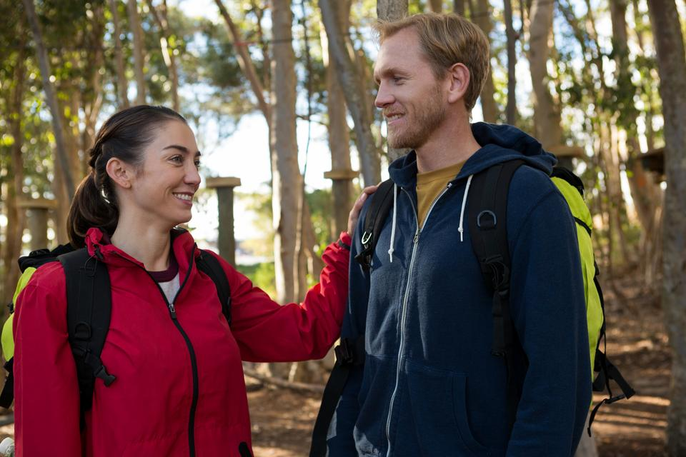 """""""Woman keeping her hand on man shoulder standing in forest"""" stock image"""