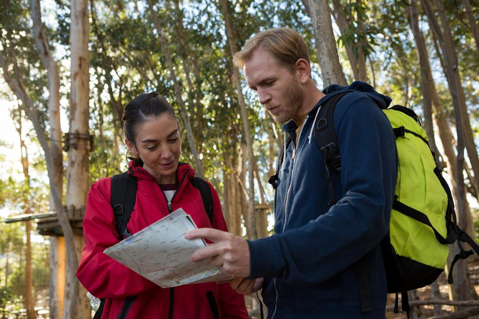 """Woman and man hiker with backpack reading map"" stock image"