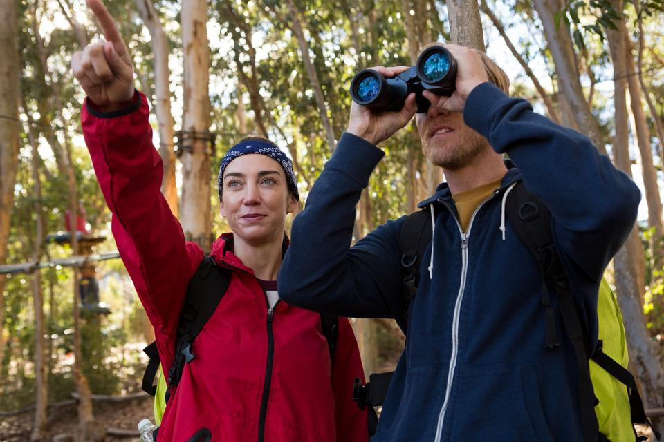 """""""Woman pointing out while man using binoculars"""" stock image"""