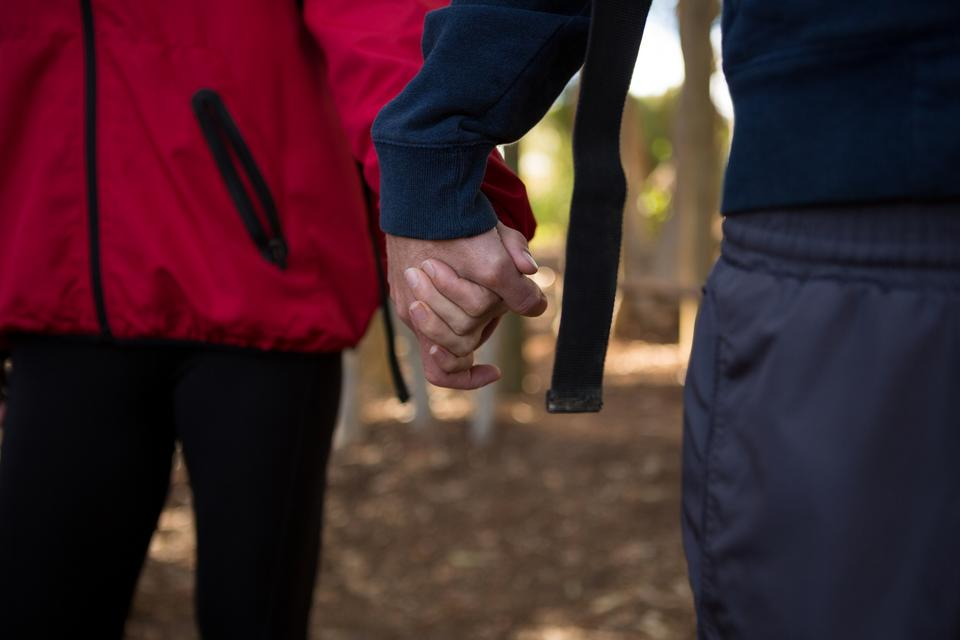 """Man and woman holding there hands in the forest"" stock image"