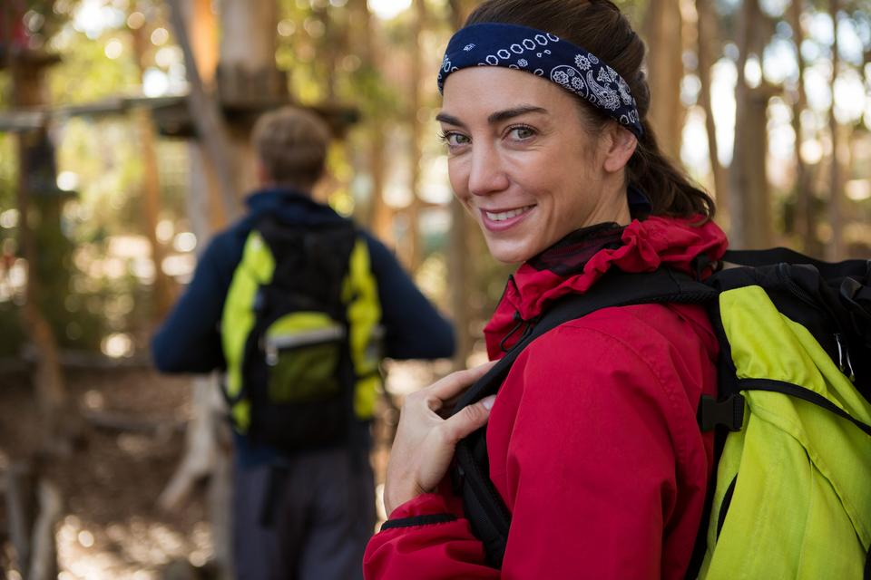 """""""Woman with backpack smiling man walking in background"""" stock image"""
