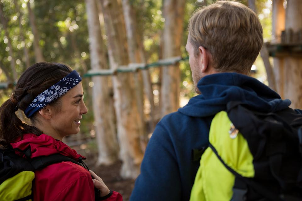 """Man and woman looking at each other while hiking"" stock image"