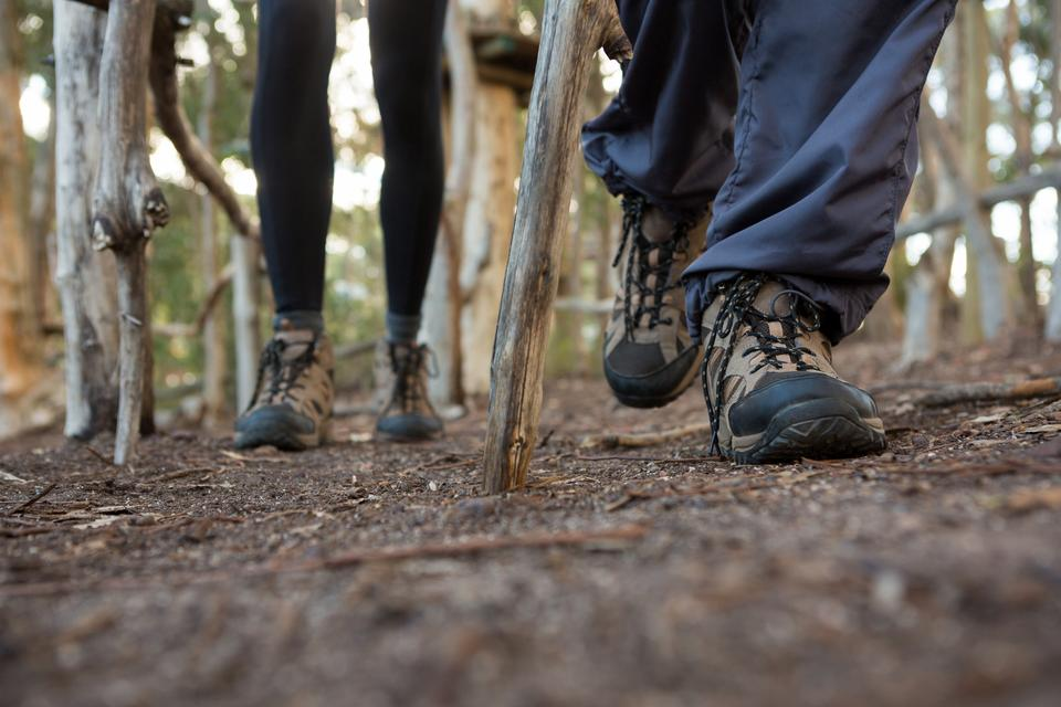 """""""Feet of woman and man hiker hiking in forest"""" stock image"""