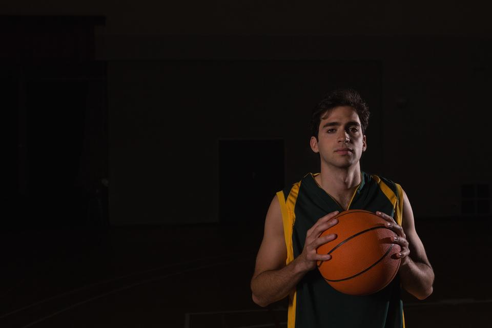 """Basketball player holding ball in the court"" stock image"