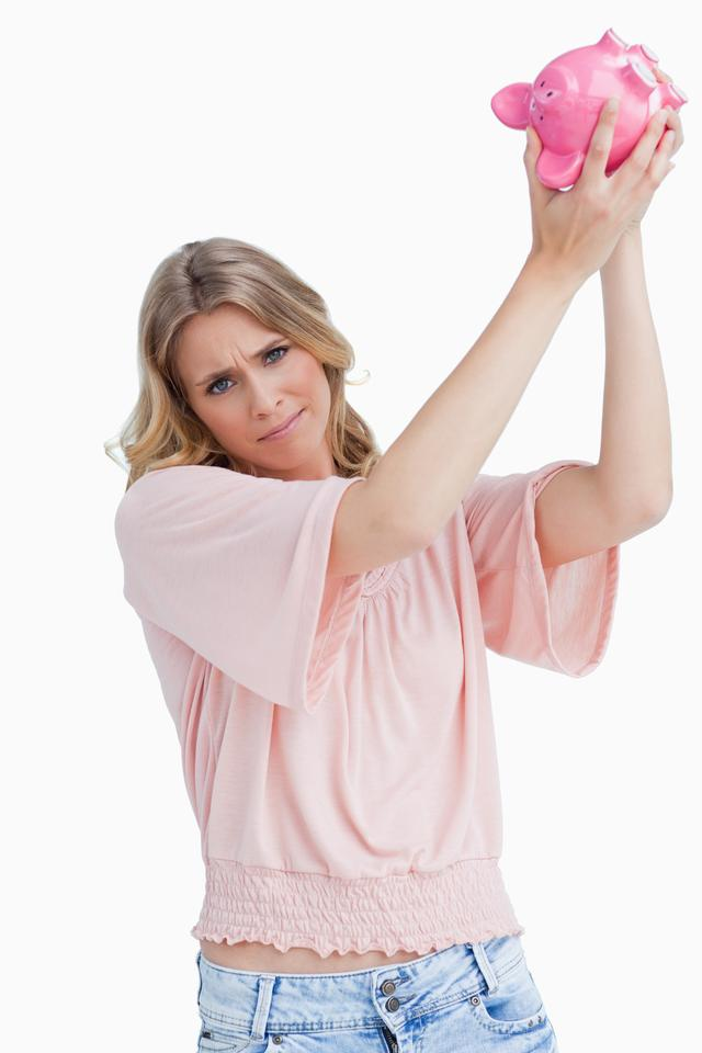 """""""Disappointed woman holds a piggy bank up over her head"""" stock image"""