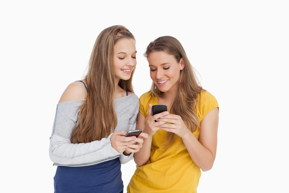 """Two young women smiling while looking their cellphones"" stock image"