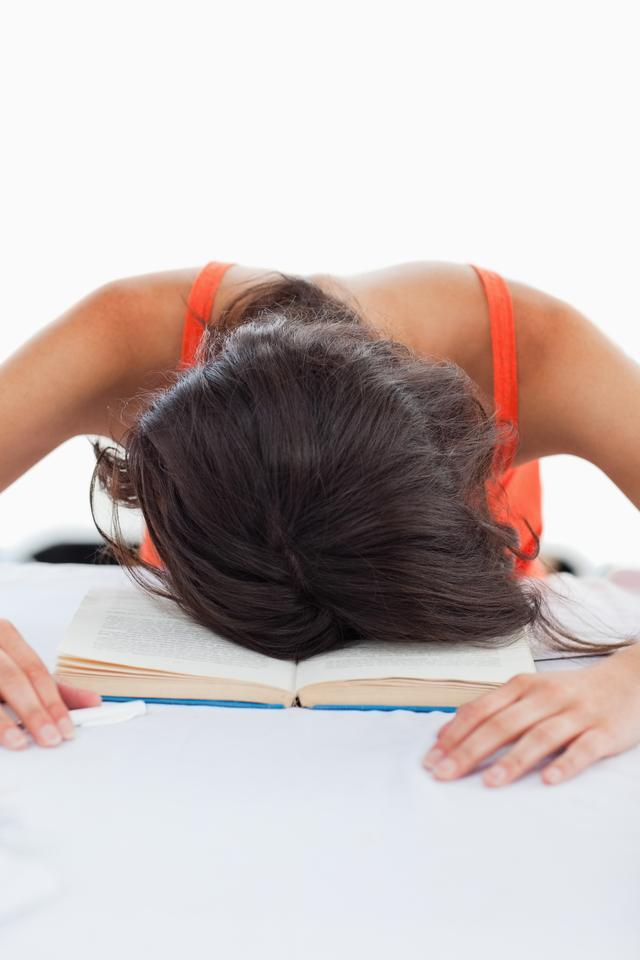 """Depressed student head on her books"" stock image"