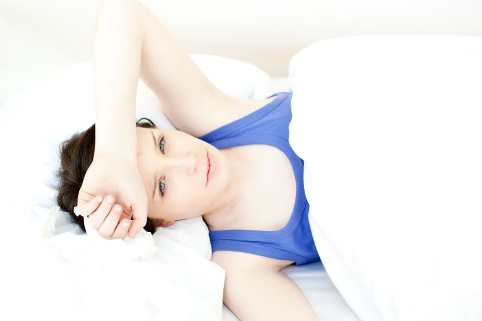"""""""Portrait of a sick young woman lying on her bed"""" stock image"""