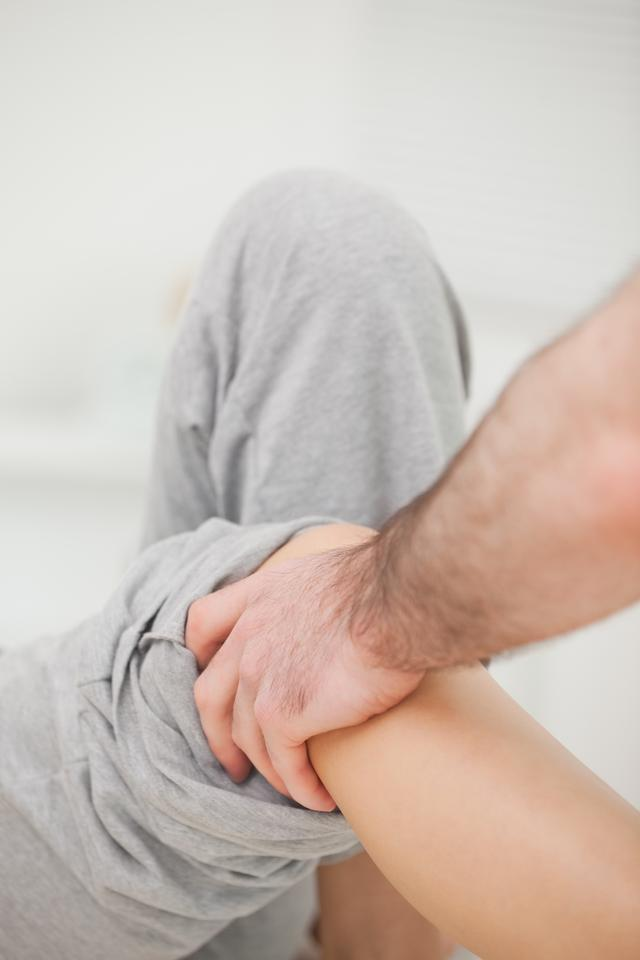 """""""Practitioner looking at the leg of his patient"""" stock image"""