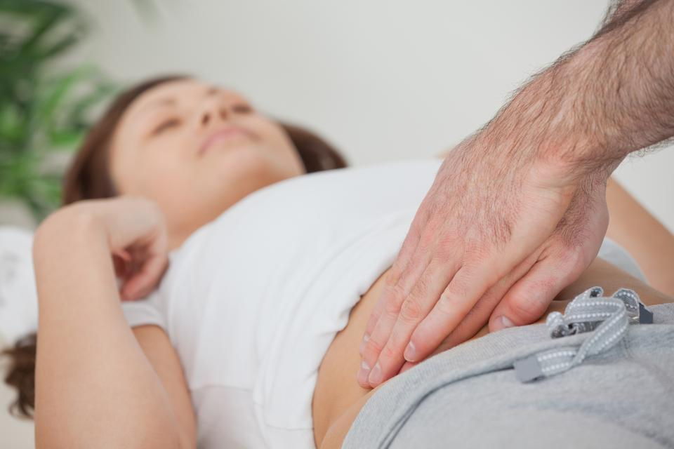 """""""Doctor examining the stomach of his patient"""" stock image"""