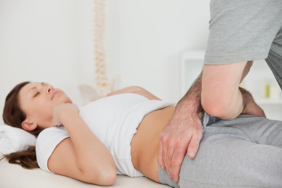 """""""Brunette woman lying while a physiotherapist touching her hips"""" stock image"""
