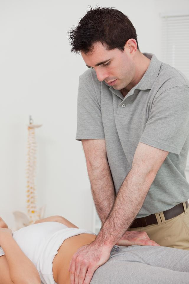 """""""Serious physiotherapist manipulating the pelvis of a patient"""" stock image"""