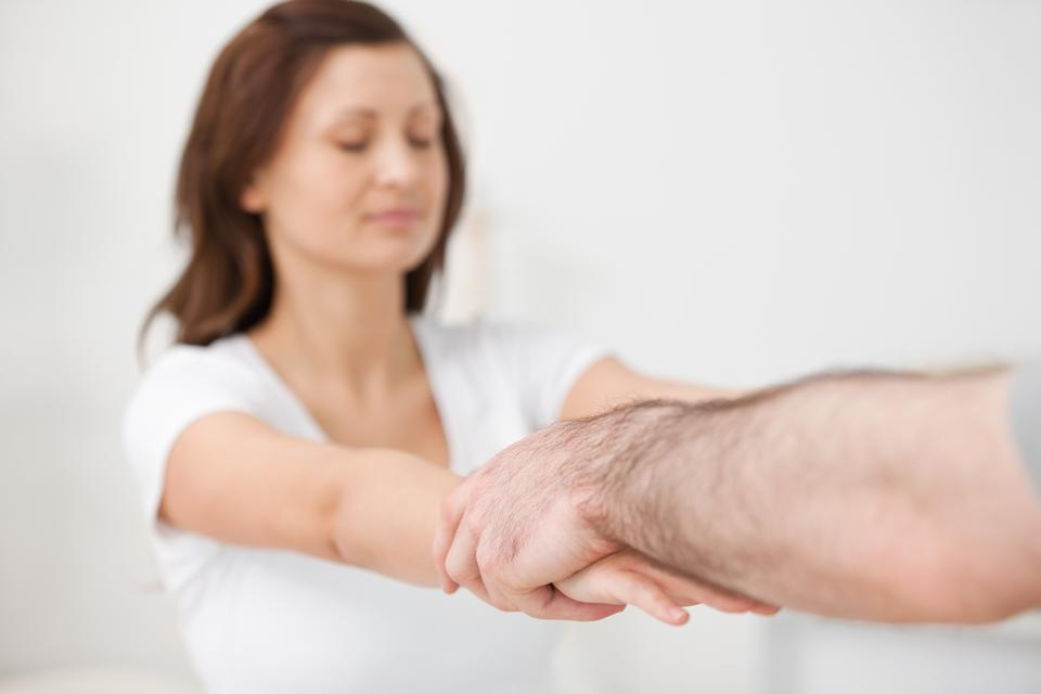 """""""Practitioner extending the arms of a patient"""" stock image"""