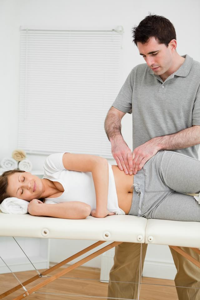 """""""Serious physiotherapist checking the pelvis of a woman"""" stock image"""