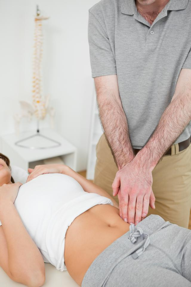"""""""Doctor examining the painful abdomen of a woman"""" stock image"""