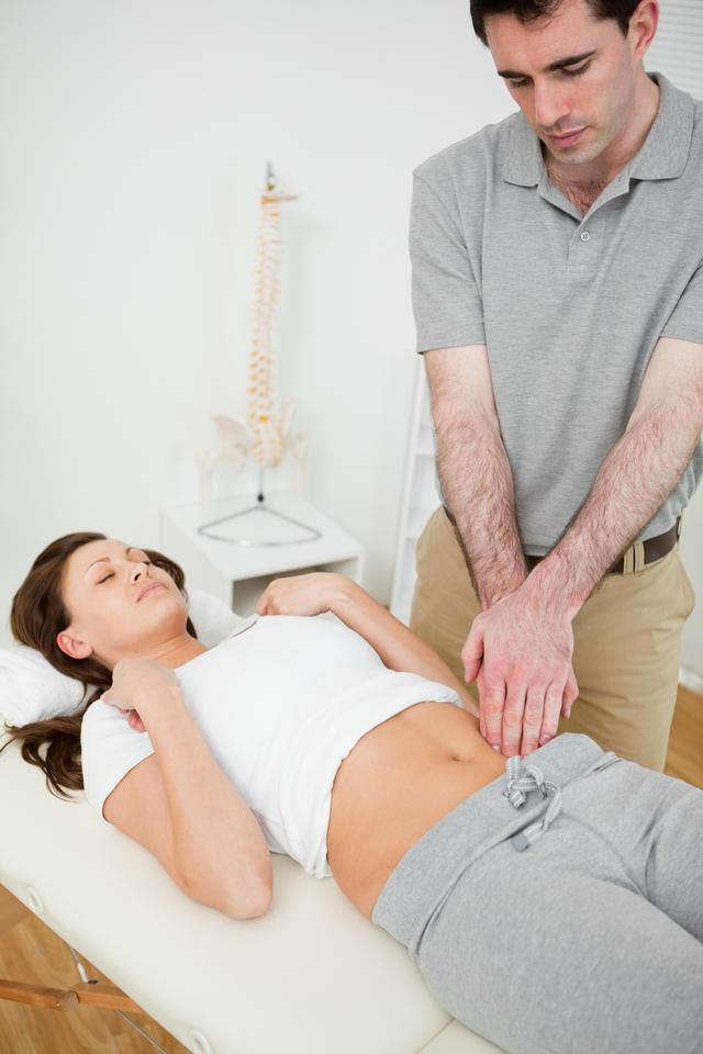 """Physiotherapist touching the abdomen of a woman"" stock image"
