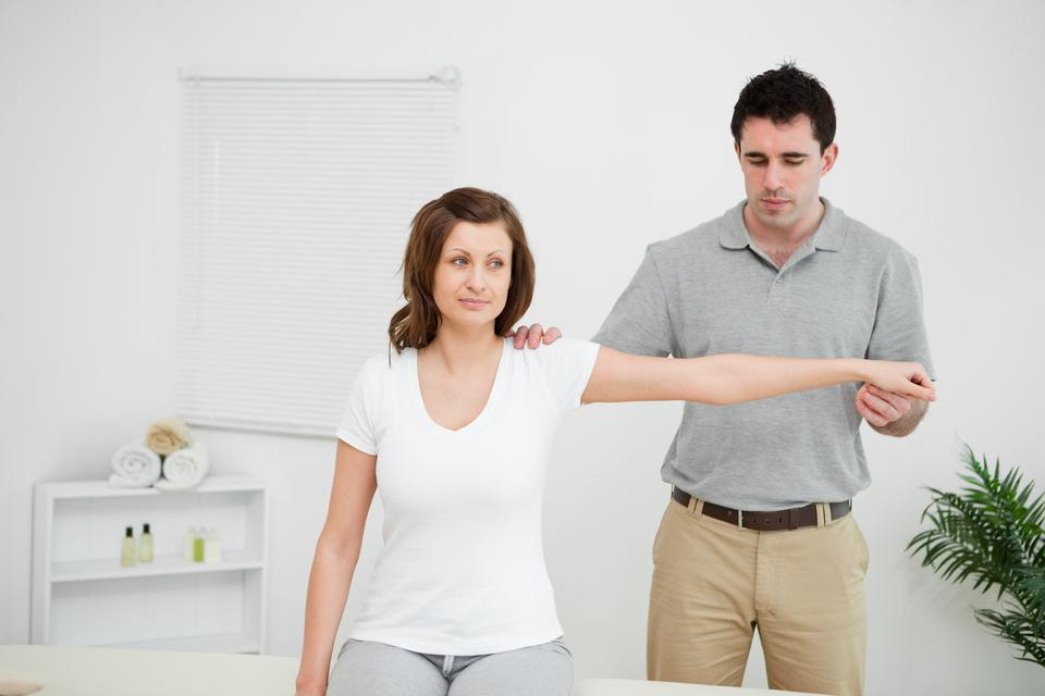 """""""Serious practitioner extending the arm of a patient"""" stock image"""