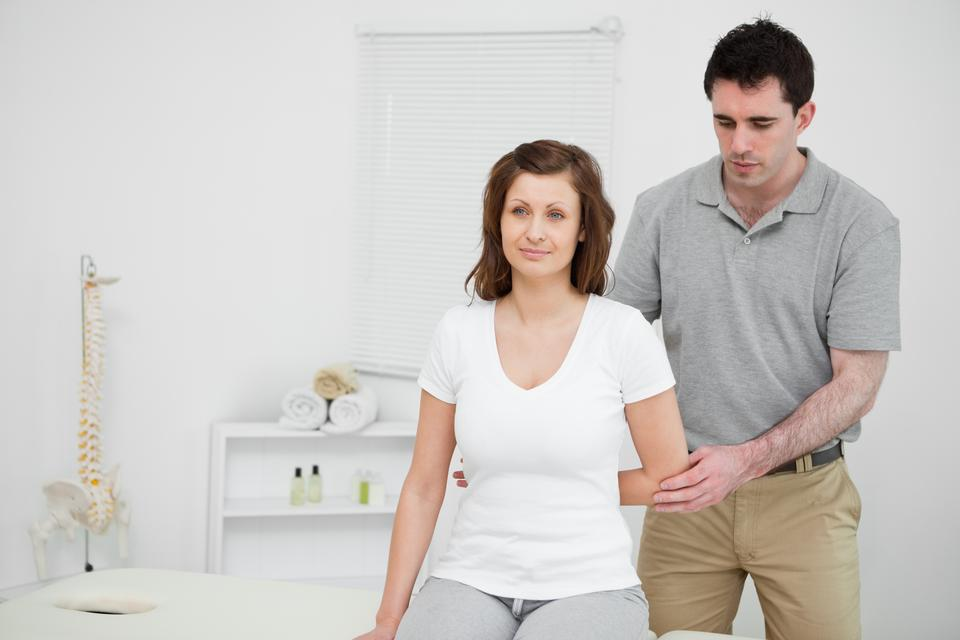"""""""Serious practitioner holding the elbow of a patient"""" stock image"""