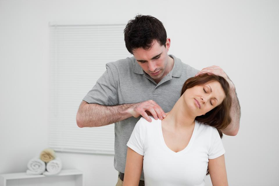"""Serious osteopath palpating the trapezius of a woman"" stock image"