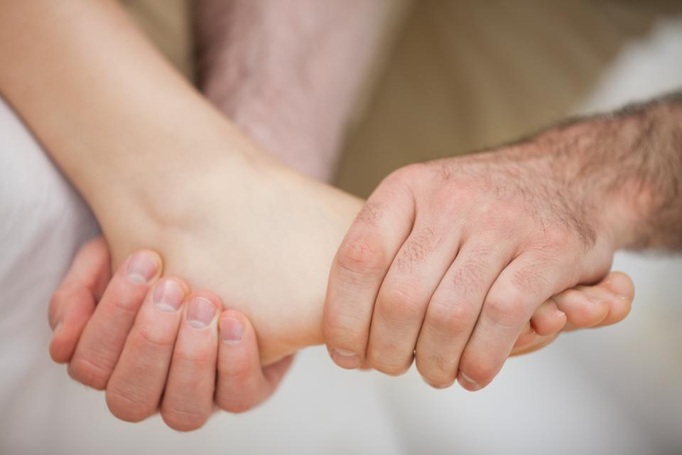 """""""Foot being held by a practitioner"""" stock image"""