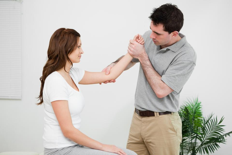 """""""Serious practitioner touching the elbow of a woman"""" stock image"""