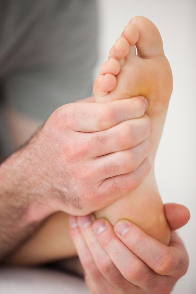 """""""Hands of a practitioner holding a barefoot"""" stock image"""