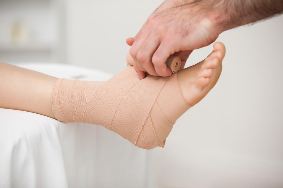 """""""Practitioner bandaging an ankle"""" stock image"""