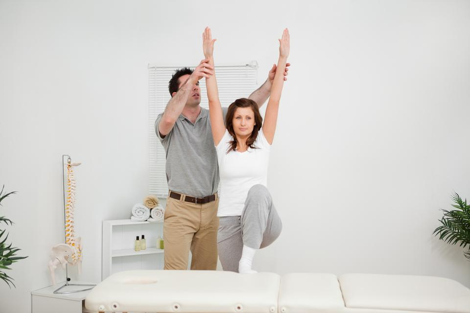 """""""Brunette doing stretching exercises with a physiotherapist"""" stock image"""