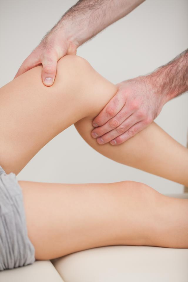 """""""Hands of a practitioner stretching a leg"""" stock image"""