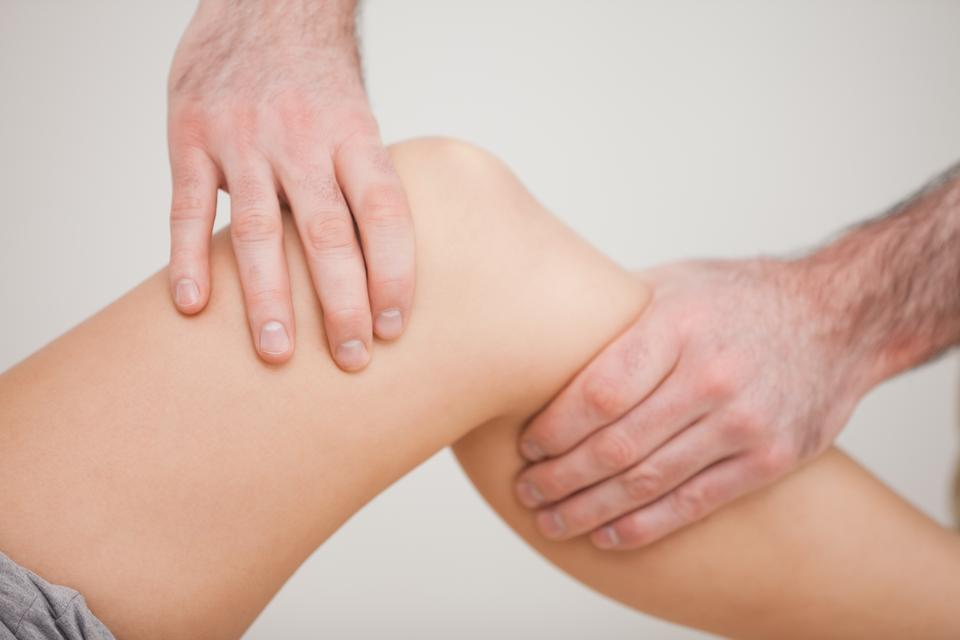 """""""Knee of a patient being touched by a practitioner"""" stock image"""