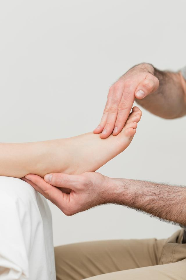 """""""Practitioner holding the foot of a patient"""" stock image"""