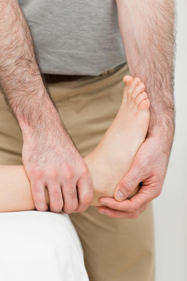 """""""Foot being manipulated by a practitioner"""" stock image"""