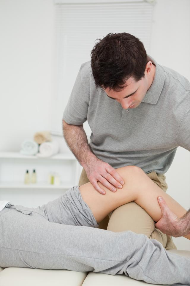 """""""Serious practitioner holding the knee of a patient"""" stock image"""