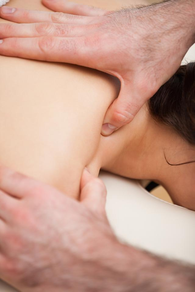 """Chiropractor massaging the shoulders of his patient while using his thumb"" stock image"
