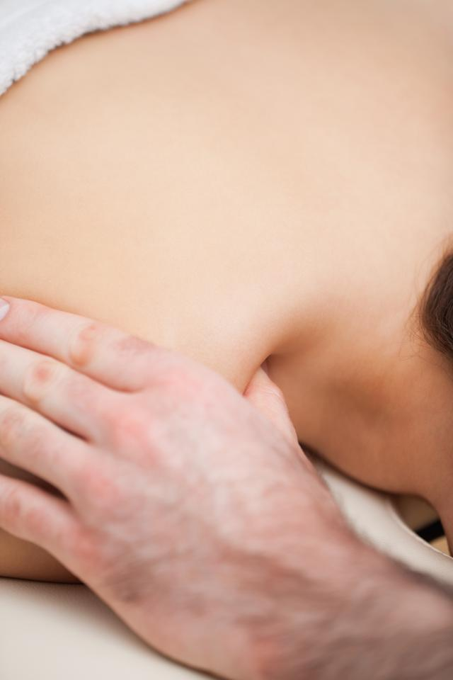 """Shoulder of a woman being massaged by a doctor"" stock image"