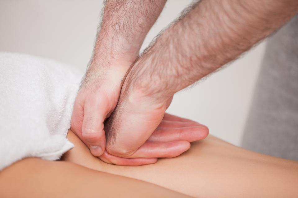 """""""Practitioner massaging the thigh of his patient"""" stock image"""