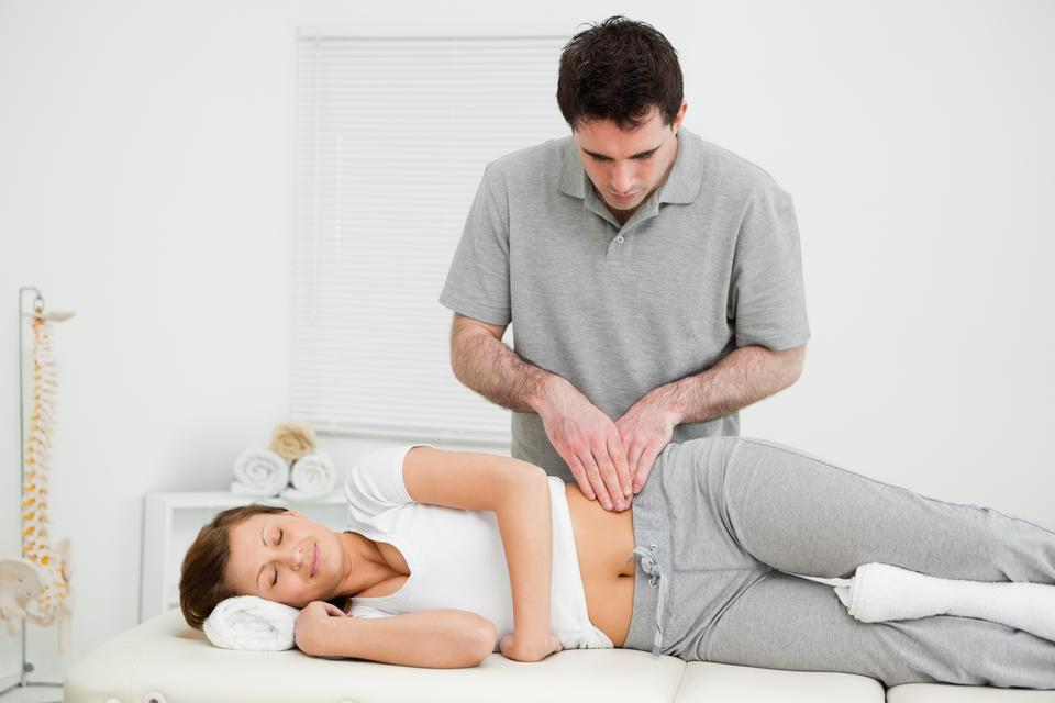 """""""Peaceful woman being massaged on her hip by a doctor"""" stock image"""
