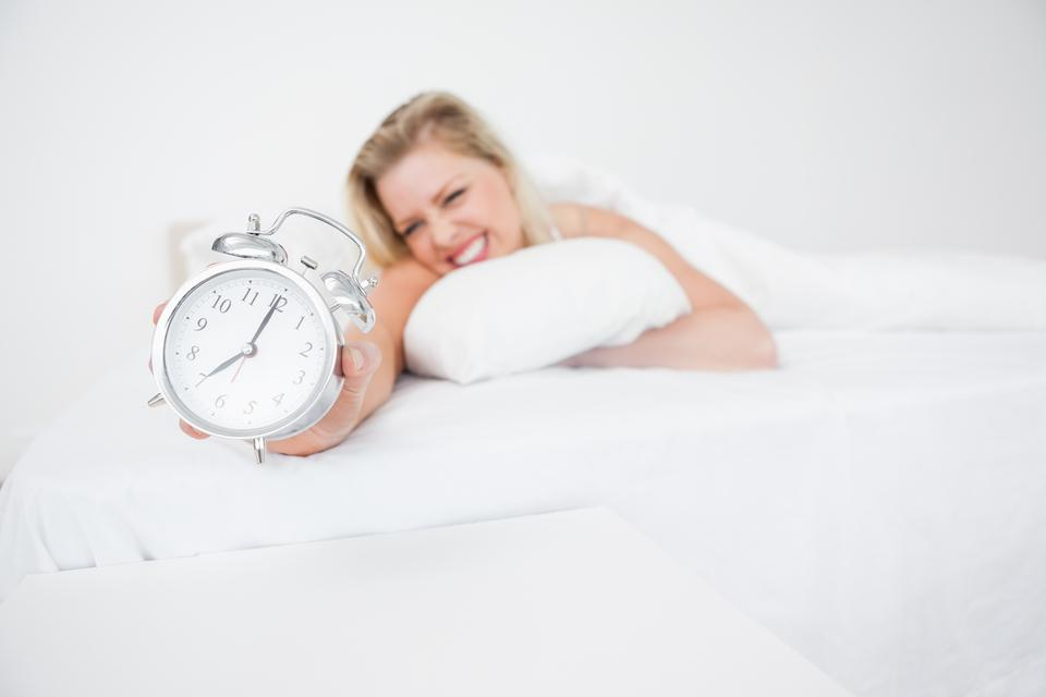 """Woman getting her alarm clock"" stock image"